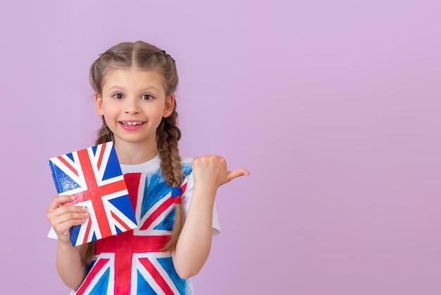 Девушка держит в руках учебник английского языка и показывает большим пальцем в сторону. изолированный фон.