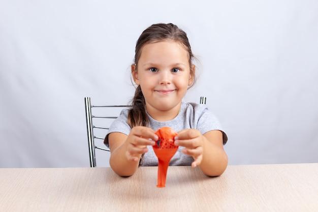 女の子は膨らんだ風船を持って、笑顔で白い背景のテーブルに座っています。