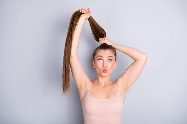 Девушка держит волосы в хвосте руками