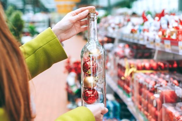 소녀는 그녀의 손에 크리스마스와 새해 장식용 장식 볼이 달린 병을 보유하고 있습니다.