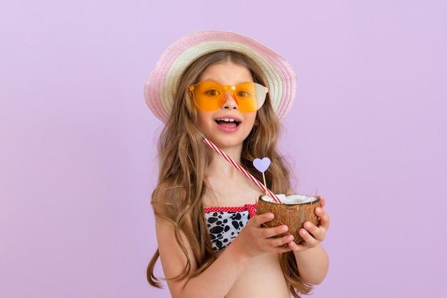 소녀는 코코넛에 부은 칵테일을 손에 들고 있습니다.