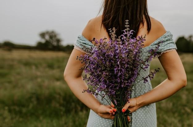 Девушка держит в руках за спиной большой букет сиреневых и фиалковых цветов.