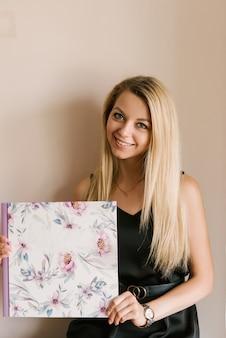 女の子は春のスタイルで美しいフォトアルバムや写真集を手に持っています