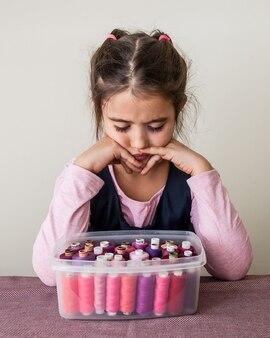 У девочки много ниток разных ярких цветов.