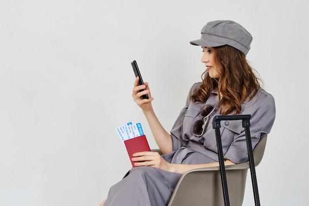 Девушка держит билеты на самолет с багажом и паспортом и смотрит на смартфон.