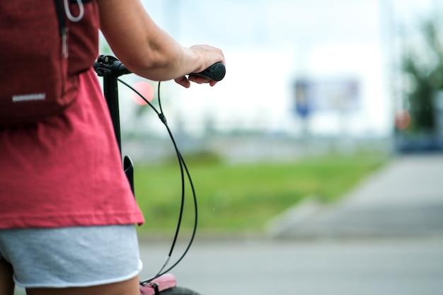 女の子は美しいスタイルで自転車のハンドルバーを保持しています。