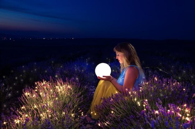 소녀는 달을 손에 쥐고 있습니다. 밤에 라벤더 밭입니다.