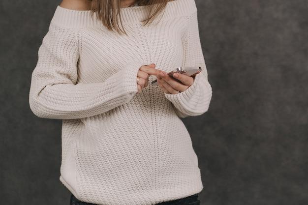소녀는 그녀의 손에 전화를 보유하고 있습니다. 소셜 네트워크에 대한 의존. 가제트의 모든 삶.