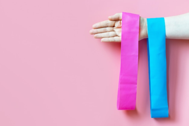 Девушка держит две фитнес-резинки, эспандер на розовом фоне, копия места