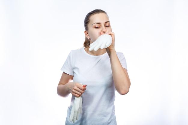 女の子は白い医療用手袋を手に持っています。細菌やウイルスに対する保護。彼女は白い背景に白いtシャツを着ています。