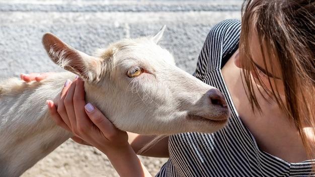 女の子はヤギを抱きしめます。動物への愛