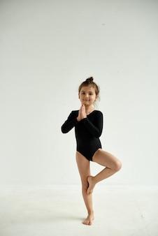黒のスーツを着た女の子は、体操から新しい動きを学びます。