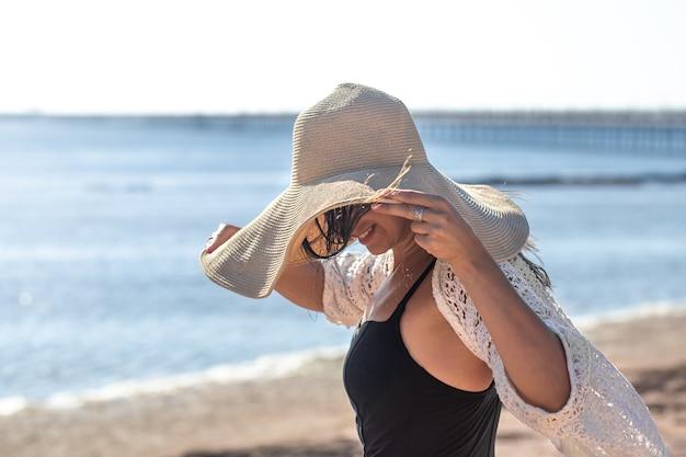 수영복 입은 소녀는 큰 모자로 얼굴을 가렸다. 바다에서 여름 휴가 개념.