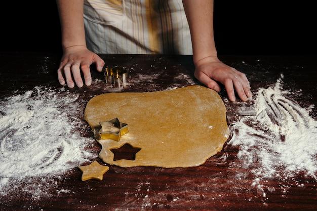 Девушка в фартуке режет на деревянном столе печенье в виде звездочек. крупный план.
