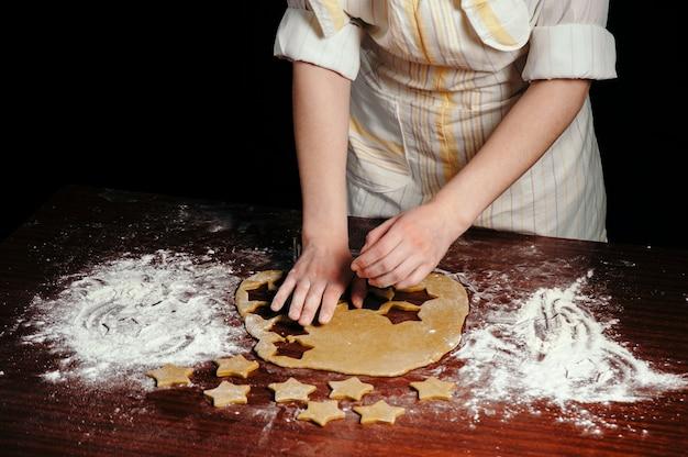 Девушка в фартуке режет на деревянном столе печенье в виде звездочек. крупный план