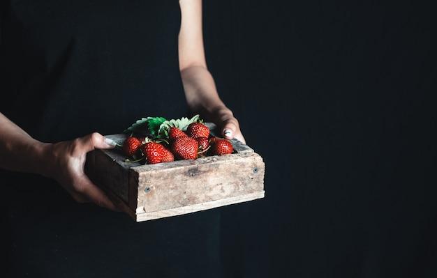エプロンの女の子は、赤い新鮮なイチゴが入った木製の箱を持っています。ジューシーな夏のベリー。ビタミン、エコフード。
