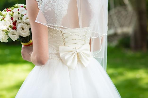 後ろに弓が付いているエレガントな白いウェディングドレスの女の子。