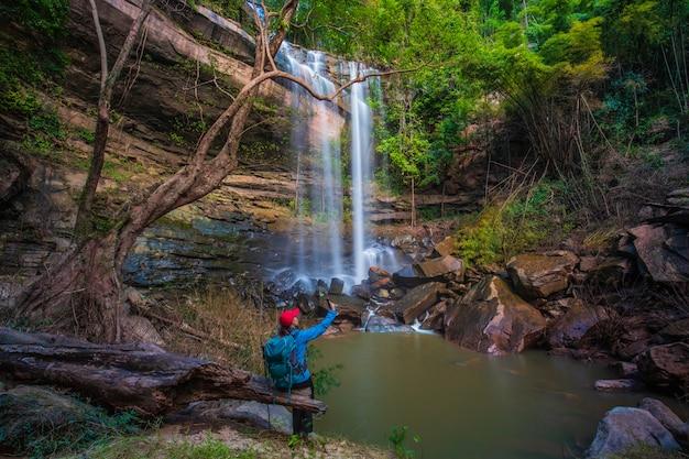 Девушка в голубом свитере путешествуя на водопаде yung thong, красивом водопаде в провинции udonthani, thailand.