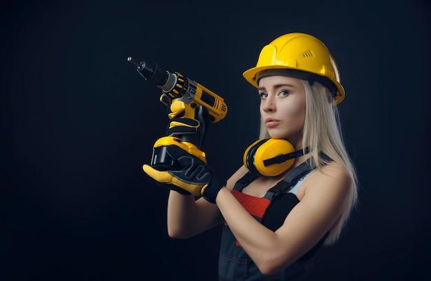 Девушка в строительной одежде и защитном снаряжении позирует с отверткой