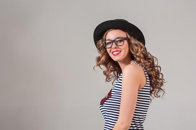 Девушка в очках и шляпе на сером