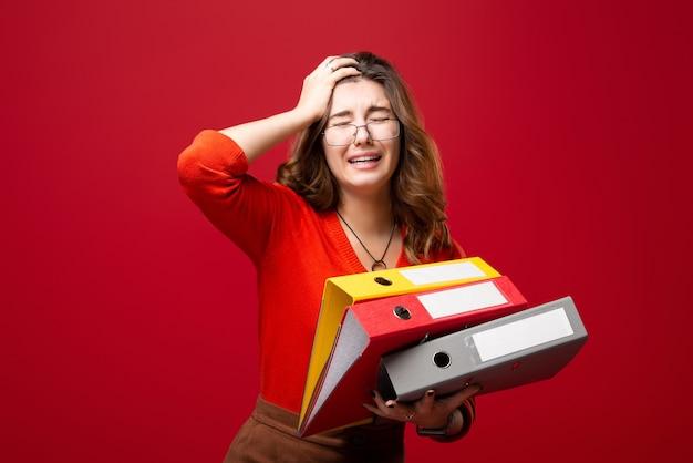 Девушка в очках несет папки, с паникой на лице на красном