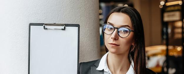 Девушка в очках показывает буфер обмена. белый чистый лист бумаги.