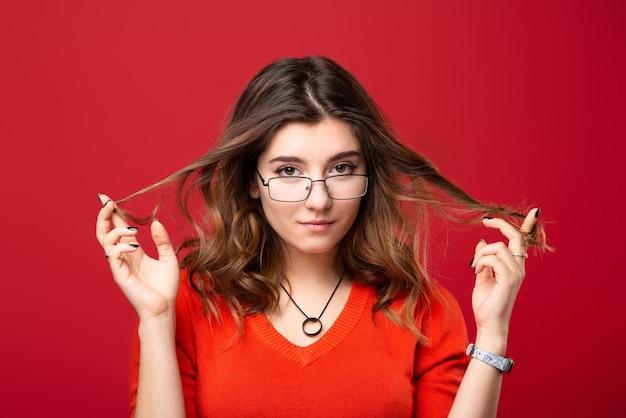 眼鏡をかけた少女は、赤に指で髪をねじります。