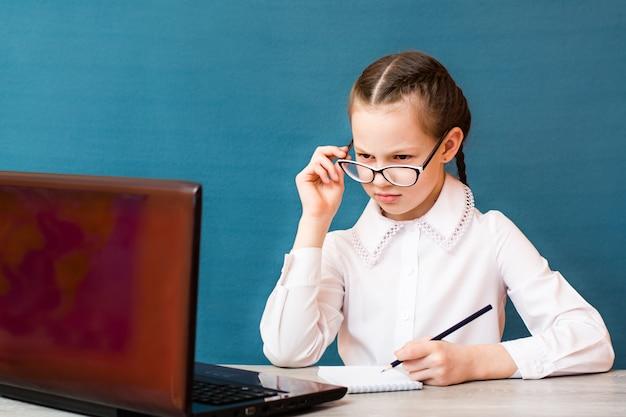 Девушка в очках работает за ноутбуком и делает заметки в блокноте за столом