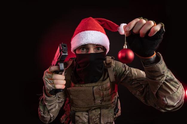 ネオンの光のかすみの暗い背景に彼の手で銃を持ってポーズをとる軍のオーバーオールのエアガンの女の子
