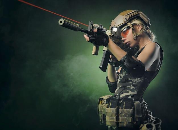 Девушка в военном комбинезоне страйкбол позирует с пистолетом в руках на темном фоне