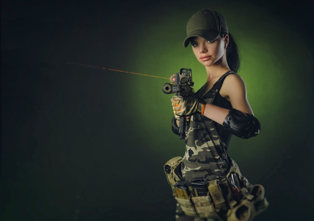 Девушка в военной спецодежде позирует с пистолетом в руках на темном фоне в дымке