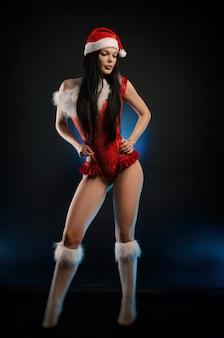 빨간 크리스마스 바디수트와 산타클로스 모자를 쓴 소녀
