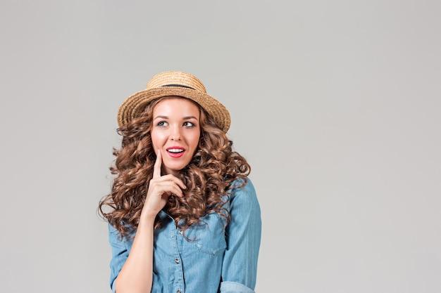 회색 스튜디오 벽에 밀짚 모자 소녀