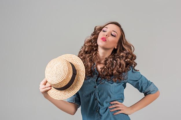 회색 벽에 밀짚 모자 소녀