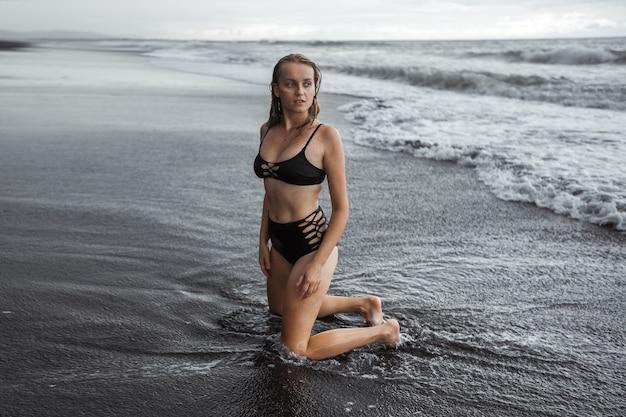 Девушка в черном купальнике на черном песке стоит на коленях