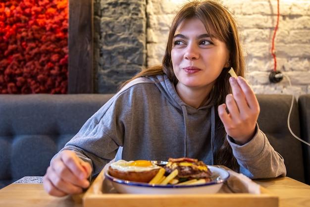 カフェの女の子は大きなハンバーガーとフライドポテトを楽しんでいます。
