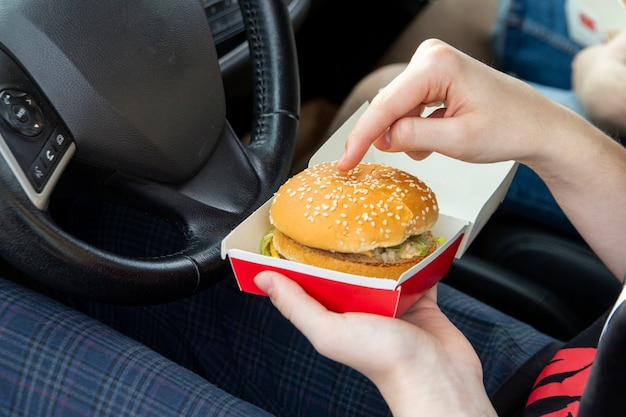 Девушка в машине держит в руках бургер фастфуд закуски на вынос в дороге