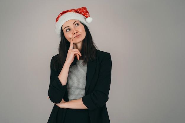 クリスマスの帽子をかぶった女の子。男はクリスマスを願います。ビジネスレディはあなたにメリークリスマスを願っています。