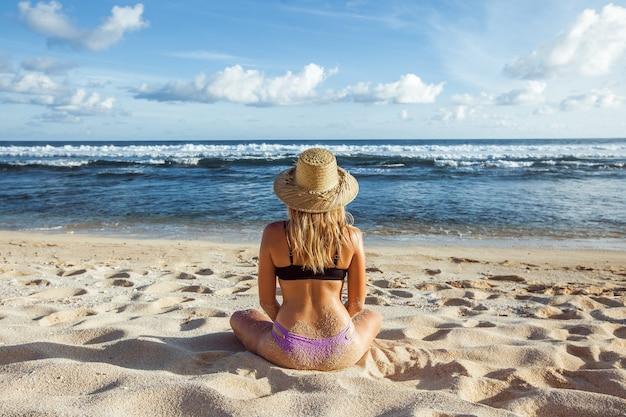Девушка в шляпе и купальнике на пляже сидит спиной к камере и смотрит на океан.