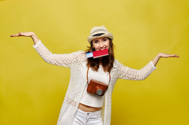 Девушка в шляпе с билетами на самолет, паспорт в зубах изображает полет.