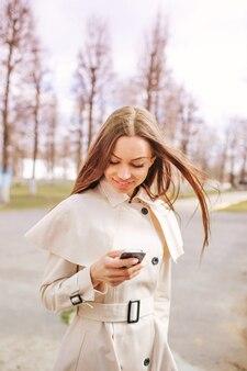 Девушка в светлом пальто аккуратно набирает номер телефона.
