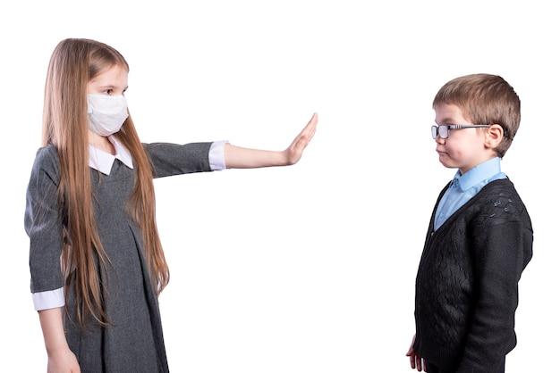 마스크를 쓴 소녀는 마스크가 없는 소년과 거리를 유지해달라고 요청합니다.