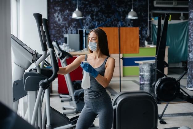 Девушка в маске дезинфицирует тренажерный зал во время пандемии