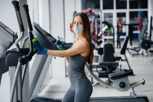 마스크를 쓴 소녀가 전염병 동안 체육관 장비를 소독합니다.