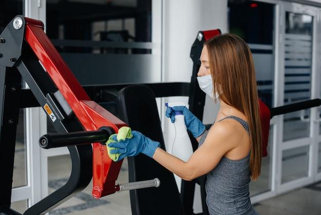 Девушка в маске дезинфицирует тренажеры во время пандемии.