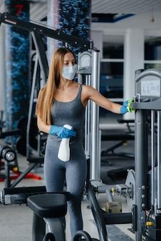 Девушка в маске дезинфицирует тренажерный зал во время пандемии.