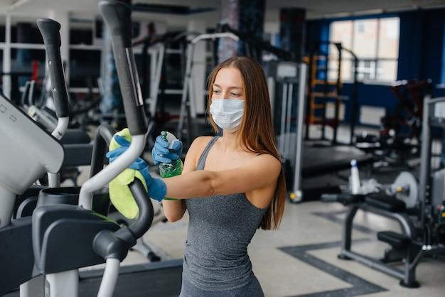 パンデミック時にジム設備を消毒するマスクの女の子。