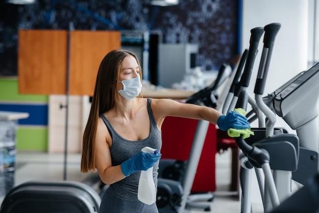 パンデミック時にジムの設備を消毒するマスクの女の子