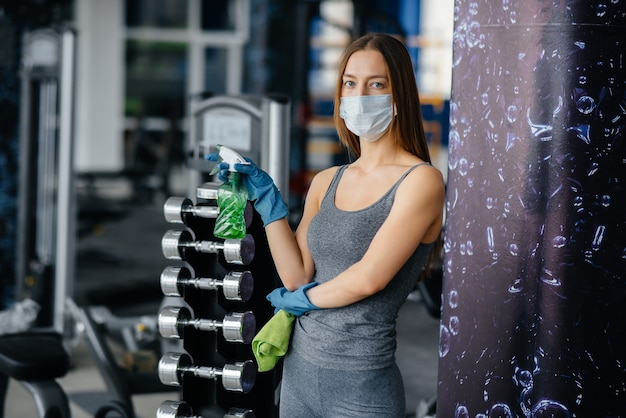 パンデミックの際に体育館の設備を消毒する仮面をかぶった少女。
