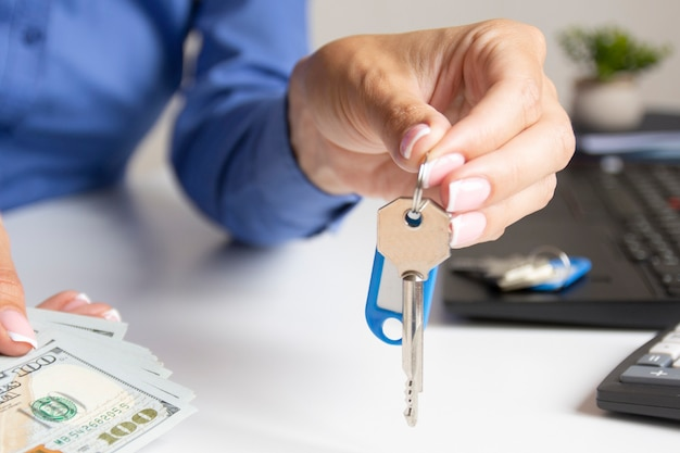 オフィスの女の子が鍵を持ってお金を渡す